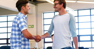 Male executives shaking hands in office
