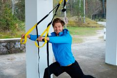 Male exercising with fitness trx strips. Smiling sporty man in a blue jacket exercising with fitness trx strips Royalty Free Stock Photography