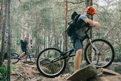 Male extreme cyclist on mountain bike showing thumb up gesture to friend with bmx. In forest royalty free stock photography