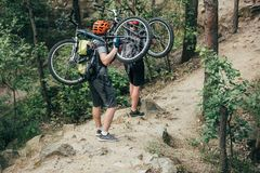 Male extreme cyclists in helmets carrying mountain bikes. In forest royalty free stock photography