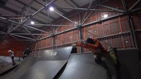 A man in orange in a jacket tries to make an invert trick, but falls. Slow motion. A male extreme in a skate park tries to do a dangerous stunt on the ramp but stock footage