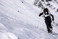 Male extreme skier heading towards a high alpine mountain peak. A male extreme skier heading towards a high alpine mountain peak with his skis strapped to his royalty free stock images