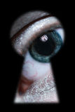 Male eye spying through a keyhole. Macro stock images