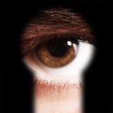 Male eye spying through a keyhole Stock Image