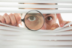 Male eyes spying through roller blind with loupe Royalty Free Stock Images
