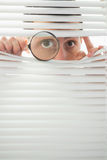 Male eyes spying through roller blind with magnifier Stock Image
