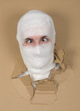 Male face on bandage in carton hole. Male face on bandage put out in carton hole stock photography