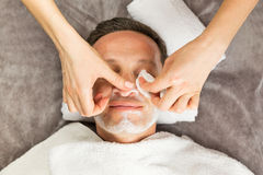 Male face with cream mask, hands of professional cosmetologist Royalty Free Stock Photos