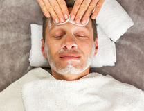 Male face with cream mask, hands of professional cosmetologist. With cotton sponges Stock Photos