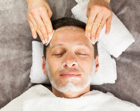 Male face with cream mask, hands of professional cosmetologist Stock Images