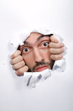 Male face through the hole. In paper royalty free stock photos