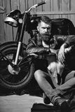 Male Face. Issues affecting boy. Bearded man hipster biker. Brutal male with beard and moustache in leather jacket sits on floor near motorcycle with bone skull Royalty Free Stock Images