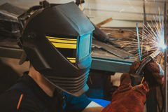 Male in face mask welds with argon-arc welding. In body shop Royalty Free Stock Image