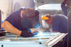 Male in face mask welds with argon-arc welding. In body shop Stock Images