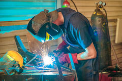 Male in face mask welds with argon-arc welding. In body shop Stock Photos