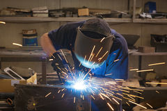Male in face mask welds with argon-arc welding. In body shop Stock Photography
