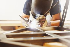 Male in face mask welds with argon-arc welding. Male in face mask, protective gloves welds with argon-arc welding. Welder makes weld seam on metal frame. Worker Royalty Free Stock Photography