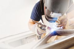 Male in face mask welds with argon-arc welding. Male in face mask, protective gloves welds with argon-arc welding. Welder makes weld seam on metal frame. Worker Royalty Free Stock Image