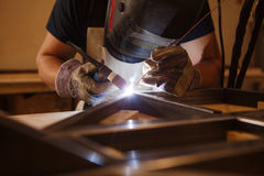 Male in face mask welds with argon-arc welding. Male in face mask, protective gloves welds with argon-arc welding. Welder makes weld seam on metal frame. Worker Royalty Free Stock Images