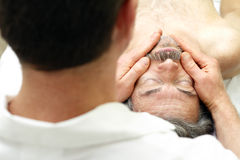 Male Face Massage. Mature man getting face massaged by a male massage therapist at a healthy spa Royalty Free Stock Photo