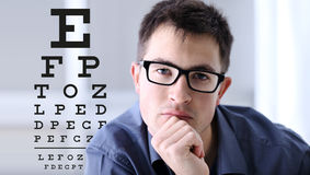 Male face with spectacles on eyesight test chart background. Eye examination ophthalmology concept Stock Photo