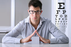 Male face with spectacles on eyesight test chart background. Eye examination ophthalmology concept Stock Photos
