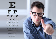 Male face with spectacles on eyesight test chart background, sho. Wing like hand, eye examination ophthalmology concept Stock Images