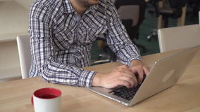 Male without face working on computer. Unrecognizable man with beard computing on laptop. On the wooden desk cup with drink stock footage