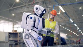Male factory employee is switching a robot on after which it snads up and starts drilling stock footage