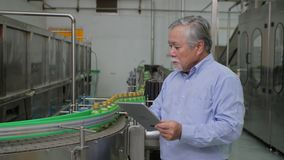 A male factory manager in beverages manufacturing industry checking the quality of the product. A male factory manager in beverages manufacturing industry stock footage