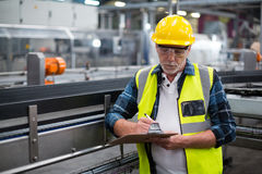 Male factory worker maintaining record on clipboard Royalty Free Stock Images