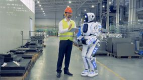 Male factory worker is remotely controlling the robot and they are walking together. 4K stock video