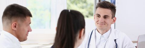 Male family doctor listen carefully young Stock Image