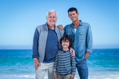 Male family members posing at the beach Stock Photo
