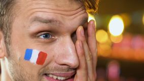 Male fan with French flag on cheek upset about favorite sports team losing game