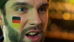 Male fan with German flag on cheek upset about favorite sports team losing game