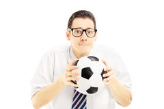 Male fan with tie holding a soccer ball and waiting for score Stock Image