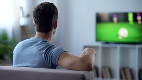 Male fan watching football match on tv, upset by poor quality digital television