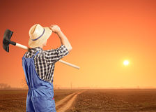 Male farmer holding a shovel. A male farmer holding a shovel and looking at a sunset Royalty Free Stock Photo