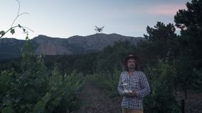 A male farmer uses a drone for farming. Monitors its grape fields. New technologies in agriculture. The copter is