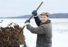 Male farmer works with manure  early spring Royalty Free Stock Photos