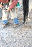 Male farrier. Male farrier working on a horseshoe inside a stable Royalty Free Stock Image
