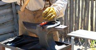Male farrier working. Male farrier working on a horseshoe outside Stock Photos