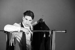 Male fashion, beauty and advertisement concept. man dressed in shirt, stands near hanger with clothes. Against green background, holds jacket, guy is choosing Stock Photography
