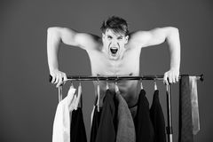 Male fashion, beauty and advertisement concept. man shouting with naked muscular torso standing at wardrobe hanger. Male fashion, beauty and advertisement Royalty Free Stock Image