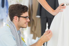 Male fashion designer adjusting dress on model Royalty Free Stock Image