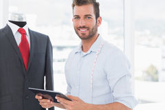 Male fashion designer with digital tablet by suit on dummy. Portrait of a young male fashion designer with digital tablet by suit on dummy in the studio Stock Image
