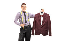 Male fashion designer holding a suit on a hanger Stock Photo