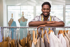 Male fashion designer leaning on rack of clothes Royalty Free Stock Image