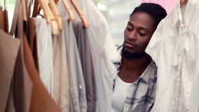 Male fashion designer looking at rack of clothes stock video footage